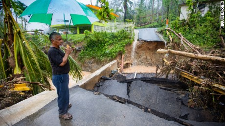 Guaynabo resident Efrain Diaz stands by a bridge washed out by rains carrying debris from Hurricane Maria.