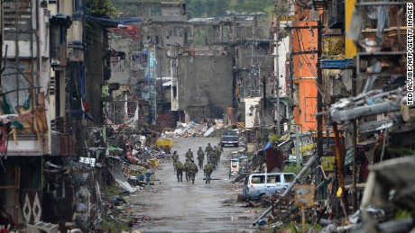 "TOPSHOT - Philippine soldiers walk past destroyed buldings in Bangolo district, after President Rodrigo Duterte declared Marawi City ""liberated"", in Marawi on October 17, 2017. Philippine President Rodrigo Duterte on October 17 symbolically declared a southern city ""liberated from terrorists' influence"" but the military said the five-month battle against militants loyal to the Islamic State group was not yet over. / AFP PHOTO / Ted ALJIBE        (Photo credit should read TED ALJIBE/AFP/Getty Images)"