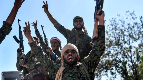 Members of the Syrian Democratic Forces (SDF), backed by US special forces, celebrate at the frontline in the Islamic State (IS) group jihadists crumbling stronghold of  Raqa on October 16, 2017 