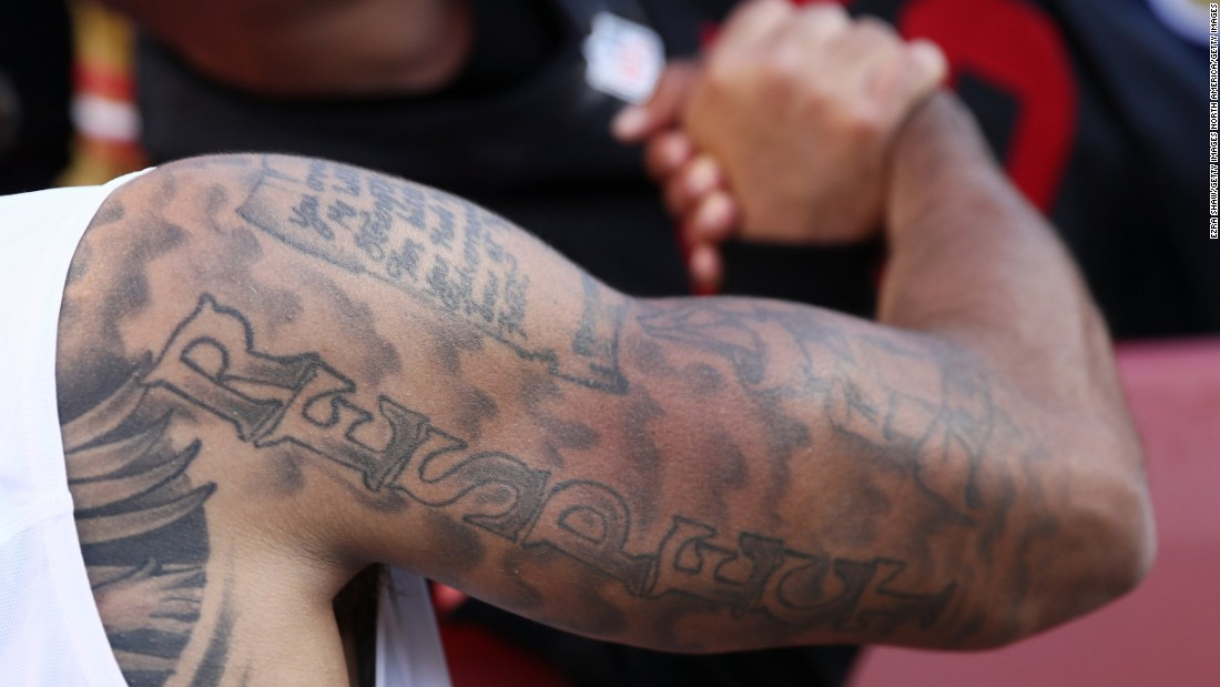 "The upper half of NFL star Colin Kaepernick's right arm is covered in ink, as is most of his torso. Across his chest is written ""Against All Odds"" while down his arm is the word ""Respect."""