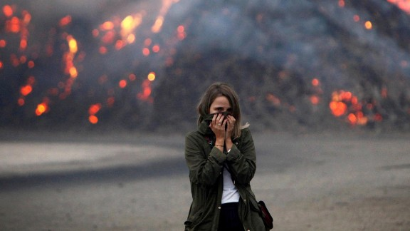 A woman in Galicia, Spain, covers her face to protect herself from the smoke.