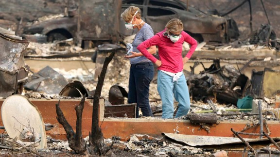 Two women sort through the rubble of a property in Napa where an elderly couple died.