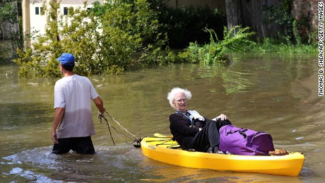 A woman is evacuated by canoe in Houston after Hurricane Harvey dumped record rainfall in 2017.