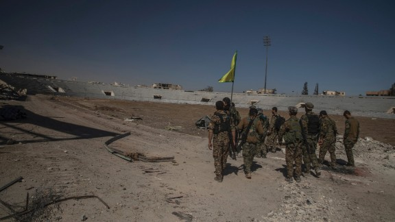 Soldiers of SDF reaching inside of stadium to put the flag.Syria, Raqqah - October 17, 2017