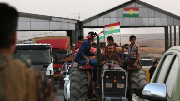 Families cross a checkpoint Monday in Altun Kupri, Iraq, as they flee violence in northern Kirkuk.