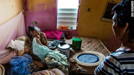Anita Ortiz waits for help, nearly a month after Hurricane Maria, in her drenched  home.