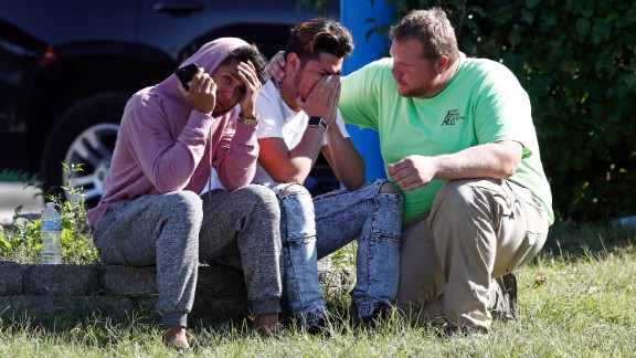 People gather across the street from the scene of a shooting at a business park in the Edgewood area on Wednesday.