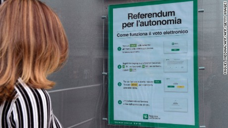 A woman in Milan looks at a poster explaining how to vote in Sunday's referendum.