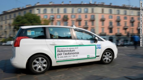 A taxi with a sticker announcing the Lombardy referendum passes along a street in Milan.
