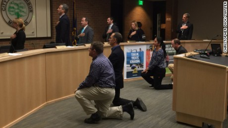 Ann Arbor City Council members Sumi Kailasapathy, Chip Smith, Jason Frenzel and Chuck Warpehoski take a knee