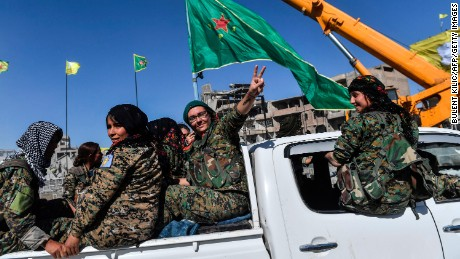 "Female members of the Syrian Democratic Forces (SDF) celebrate on the iconic Al-Naim square in Raqa on October 18, 2017, after retaking the city from Islamic State (IS) group fighters. The SDF fighters flushed jihadist holdouts from Raqa's main hospital and municipal stadium, wrapping up a more than four-month offensive against what used to be the inner sanctum of IS's self-proclaimed ""caliphate"". / AFP PHOTO / BULENT KILIC        (Photo credit should read BULENT KILIC/AFP/Getty Images)"