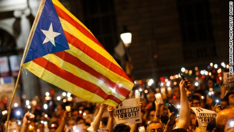 People hold candles and a Catalan pro-independence 'Estelada' flag during a demonstration in Barcelona against the arrest of two Catalan separatist leaders on October 17, 2017.