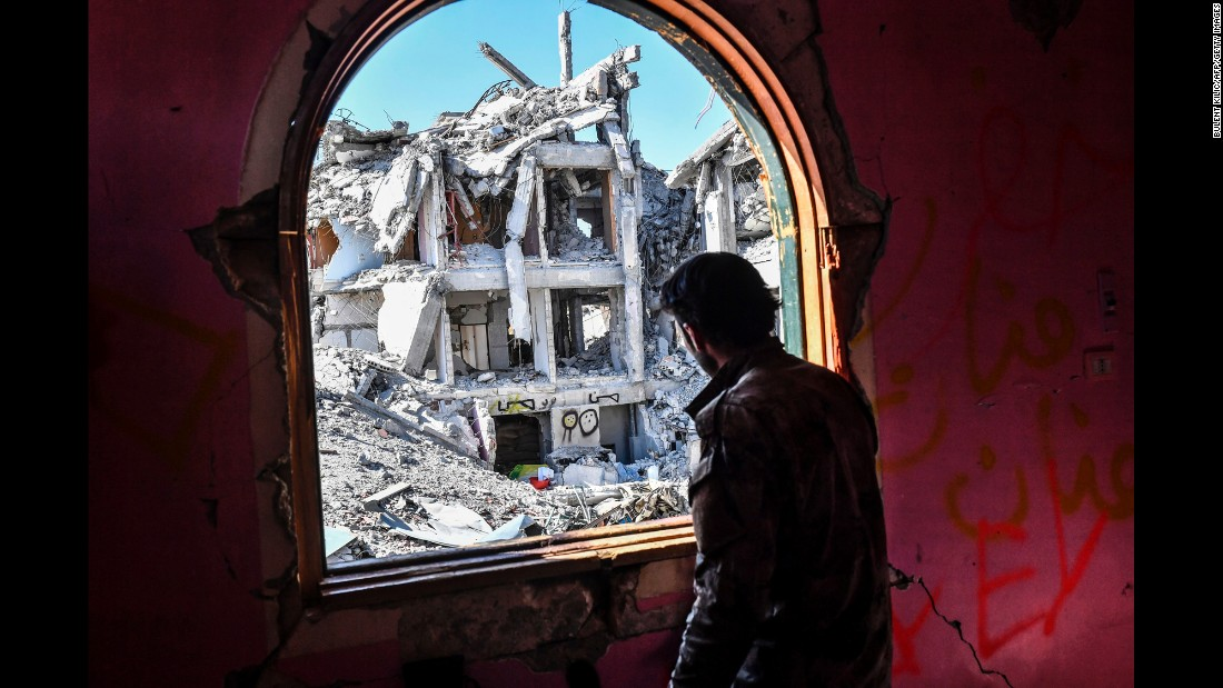 "A member of the US-backed Syrian Democratic Forces looks out at destruction in Raqqa, Syria, on Monday, October 16. ISIS had declared Raqqa as its stronghold, but SDF fighters said the embattled city would be <a href=""http://www.cnn.com/2017/10/19/middleeast/raqqa-syria-isis/index.html"" target=""_blank"">liberated in the coming days.</a>"