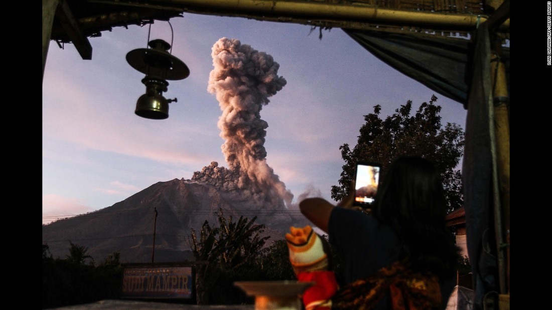 An Indonesian villager takes a picture of Mount Sinabung as it spews thick smoke on Tuesday, October 17. Mount Sinabung is one of the most active volcanoes in Indonesia.