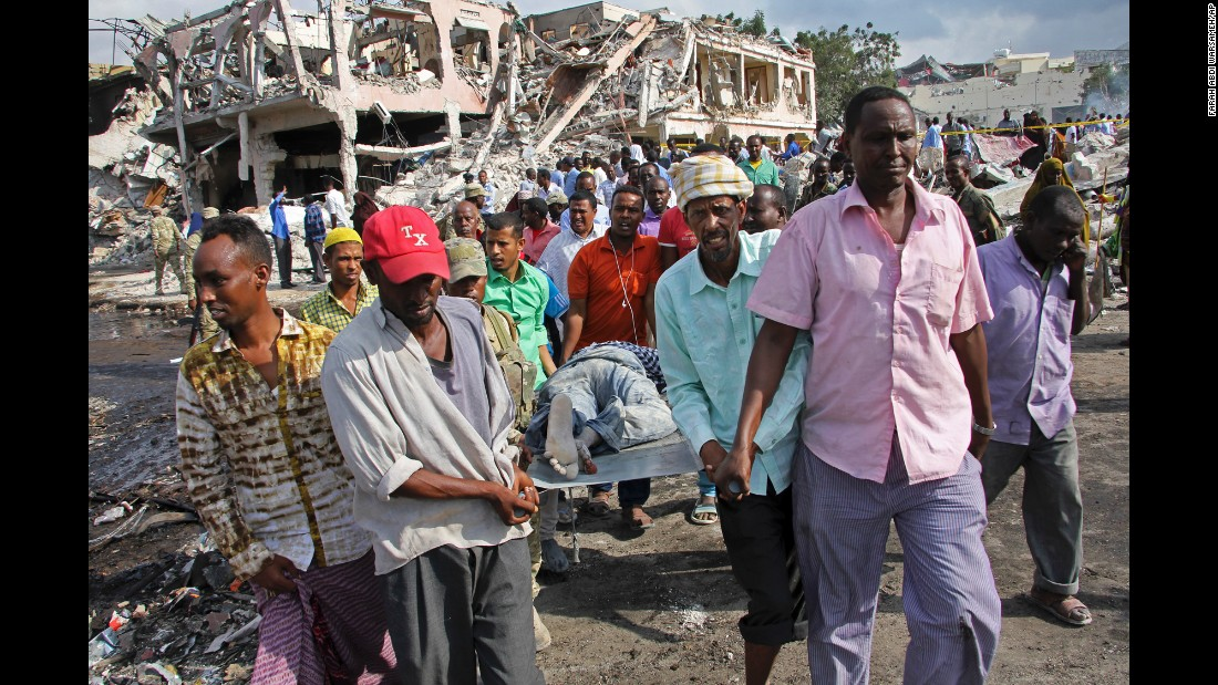 "In this Sunday, October 15, photo, men remove the body of a man killed in a <a href=""http://www.cnn.com/2017/10/16/africa/somalia-attack-deaths/index.html"" target=""_blank"">truck bombing</a> on Saturday in Mogadishu, Somalia, that killed at least 300."