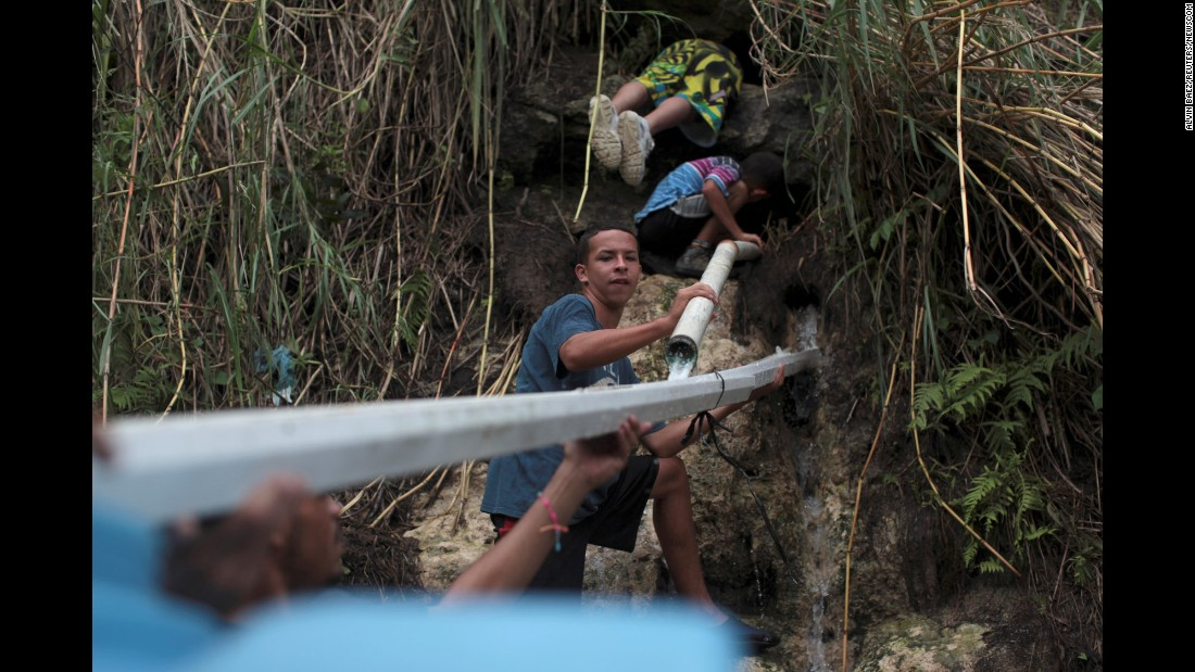 "People collect mountain spring water in Corozal, Puerto Rico, on Tuesday, October 17. One month after Hurricane Maria devastated the US territory, most of the island is still without <a href=""http://www.cnn.com/2017/10/18/health/puerto-rico-one-month-without-water/index.html"" target=""_blank"">power or clean drinking water</a>. As of Thursday the death toll remained at 48."