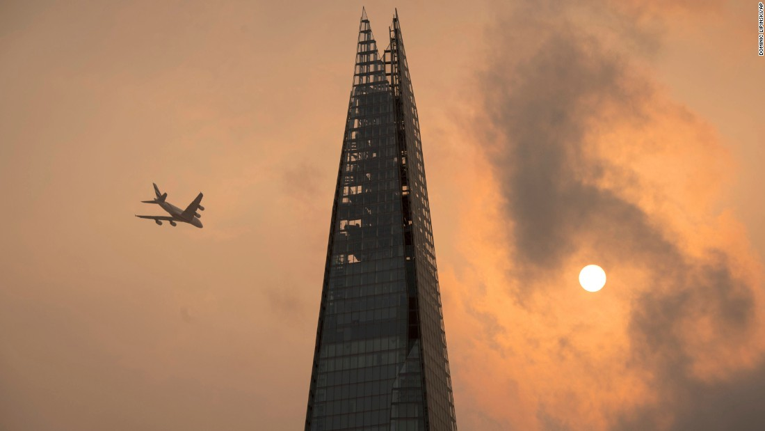 "A plane flies past the Shard in central London on Monday, October 16. The sky took on an <a href=""http://www.cnn.com/2017/10/16/health/orange-sky-uk/index.html"" target=""_blank"">orange tint</a> as dust and smoke from fires in Portugal and Spain crept north with the help of winds from Hurricane Ophelia."