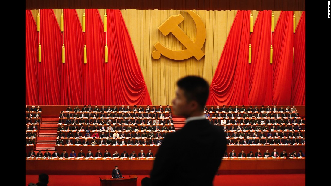 A soldier in an usher uniform stands watch as Chinese President Xi Jinping, bottom, delivers a speech at the opening ceremony of the 19th Party Congress at the Great Hall of the People in Beijing, on Wednesday, October 18.