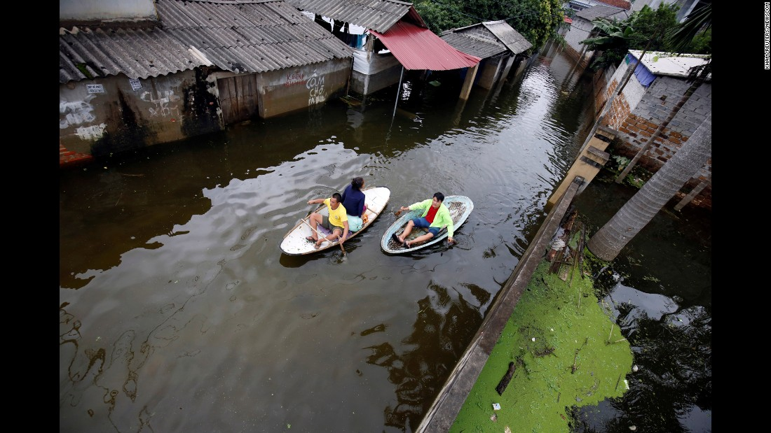 Residents paddle boats in a flooded village caused by heavy rain from a tropical depression in Hanoi, Vietnam, on Tuesday, October 17.