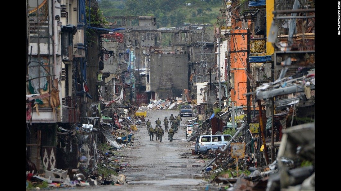 "Philippine soldiers walk past destroyed buildings in the Bangolo district after Philippine President Rodrigo Duterte declared Marawi City <a href=""http://www.cnn.com/2017/10/17/asia/duterte-marawi-liberation/index.html"" target=""_blank"">""liberated""</a> on Tuesday, October 17."