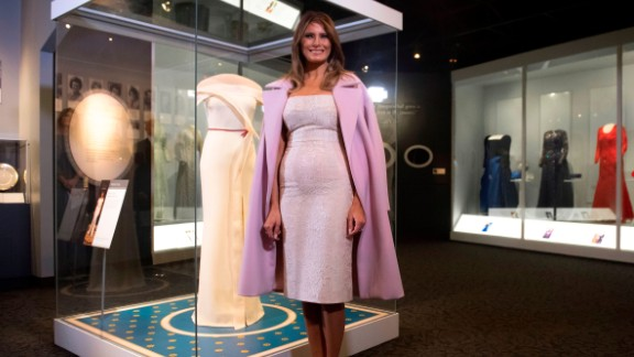 First lady Melania Trump stands alongside the gown she wore to the 2017 inaugural balls as she donates the dress to the Smithsonian's First Ladies Collection at the Smithsonian National Museum of American History in Washington on October 20, 2017.