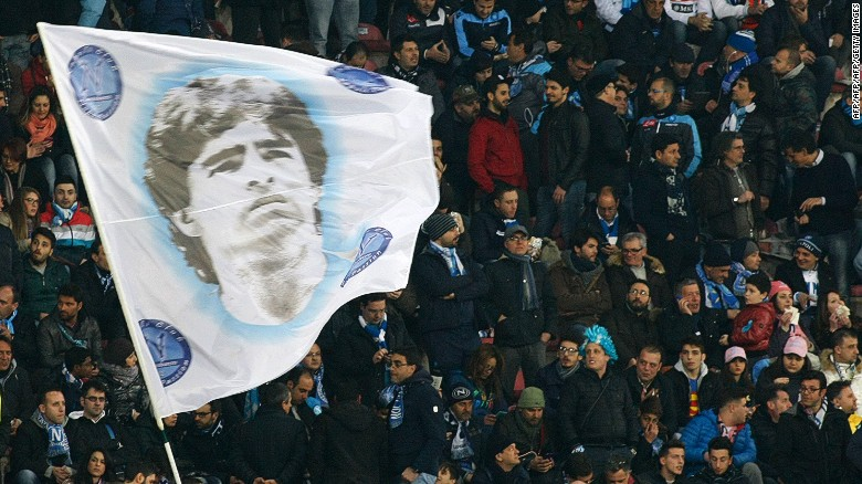 Fans of SSC Napoli wave a flag depicting former Napoli's Argentine forward Diego Armando Maradona during the Italian Serie A football match between SSC Napoli and AS Roma in San Paolo Stadium, in Naples, on March 09, 2014. AFP PHOTO/CARLO HERMANN        (Photo credit should read CARLO HERMANN/AFP/Getty Images)