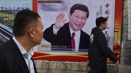 "TOPSHOT - People walk past a poster featuring Chinese President Xi Jinping with a slogan reading ""Chinese Dream, People's Dream"" beside a road in Beijing on October 16, 2017.  As Chinese leader Xi Jinping prepares to embark on a second five-year term this week, the impulsive leaders of North Korea and the United States could spoil his party. / AFP PHOTO / GREG BAKER        (Photo credit should read GREG BAKER/AFP/Getty Images)"