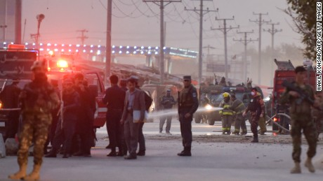 Afghan firefighters wash the road Saturday after a suicide bombing near a Kabul military academy.