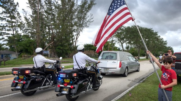 Residents watch as a hearse carrying Johnson's body makes its way to the burial site Saturday.