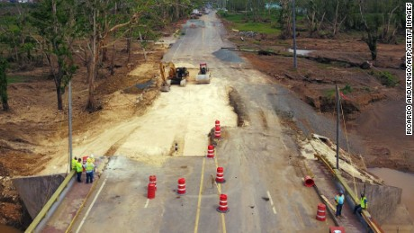 Workers repair a damaged road in Toa Alta, Puerto Rico, a month after Hurricane Maria ravaged the island.