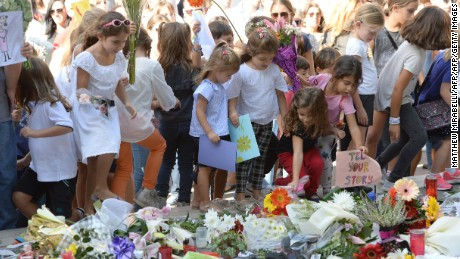 Children place cards and flowers at an informal memorial site as thousands gather during a national rally to demand justice for murdered Maltese journalist and anti-corruption blogger Daphne Caruana Galizia in the island's capital Valletta on October 22, 2017. Galizia, 53, a prominent Maltese journalist and blogger who made repeated and detailed corruption allegations against Prime Minister Joseph Muscat's inner circle, was killed by a car bomb on October 16, 2017. / AFP PHOTO / Matthew Mirabelli / Malta OUT        (Photo credit should read MATTHEW MIRABELLI/AFP/Getty Images)