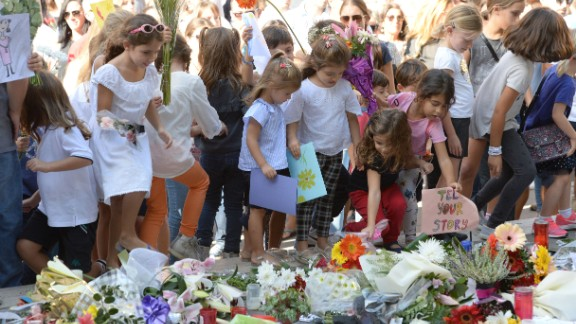 Children place cards and flowers at an informal memorial site as thousands gather during a national rally to demand justice for murdered Maltese journalist and anti-corruption blogger Daphne Caruana Galizia in the island