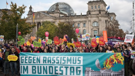 "Thousands of people gathered near the German parliament Sunday to protest against the AfD. ""Against racism in the parliament,"" reads the poster."