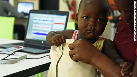 "Telecommunications engineer Olivia Koburongo fits a child with the mama-ope kit at the Makerere University of Public Health in Kampala on January 16, 2017. A team of Ugandan engineers has invented a ""smart jacket"" that diagnoses pneumonia faster than a doctor, offering hope against a disease which kills more children worldwide than any other."