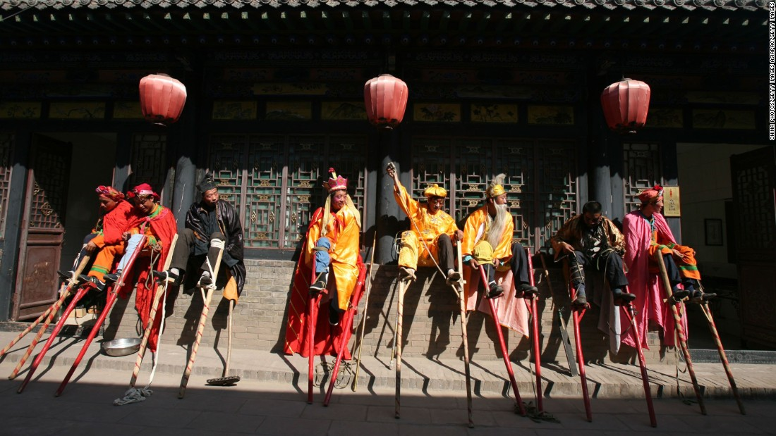 Stilt acrobats rest their (very long) legs after a street performance in Pingyao.