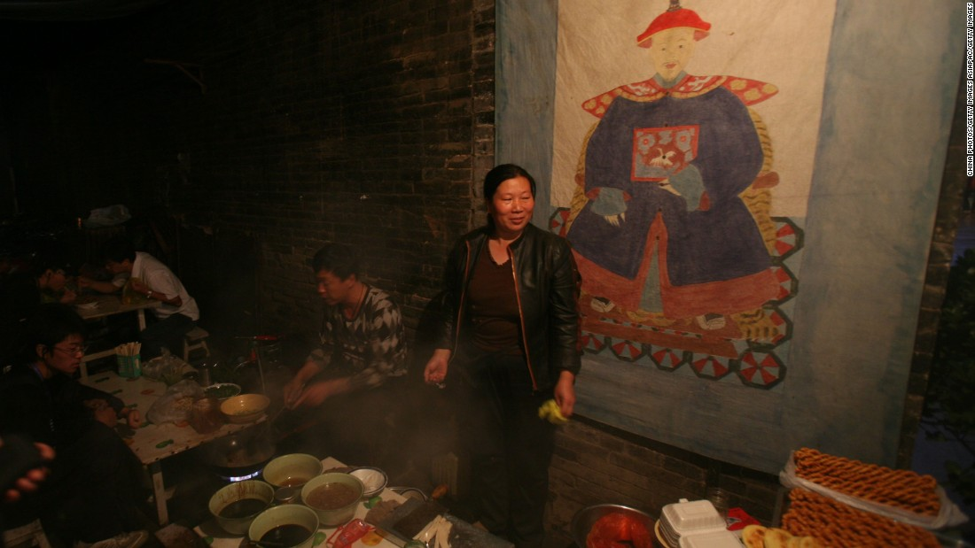 A street vendor sets out her wares under a painting of a Qing Dynasty official.