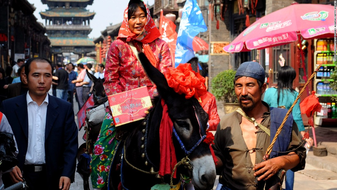 A bride dressed in traditional red robes rides a donkey through Pingyao's ancient streets.