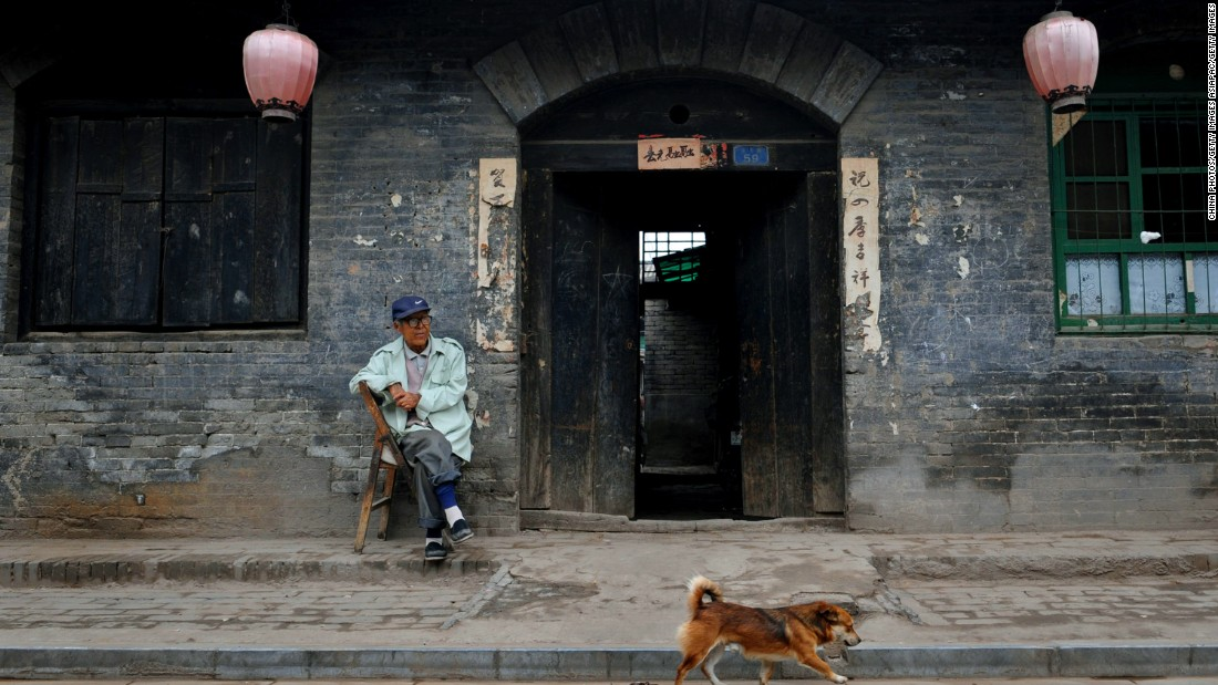 An old man rests outside his traditional-style home in Pingyao ancient city.