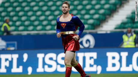 "Arizona Cardinals quarterback Drew Stanton runs on the field wearing a ""Supergirl"" outfit before an NFL football game against Los Angeles Rams at Twickenham Stadium in London, Sunday Oct. 22, 2017. (AP Photo/Matt Dunham)"