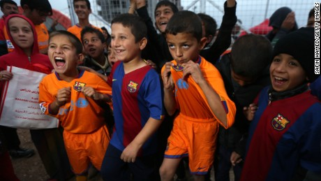 Displaced Iraqi children pose for a picture with FC Barcelona shirts  at the Harsham refugee camp, near Arbil.
