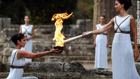 Actress Katerina Lechou (R), acting the high priestess, lights the Olympic flame at the Temple of Hera in Olympia, the sanctuary where the Olympic Games were born in 776 BC, on October 24, 2017 during the lighting ceremony of the Olympic flame for the 2018 Winter Olympics in Pyeongchang, South Korea.  The 2018 Winter Olympics will take place from February 9 until February 25, 2017. / AFP PHOTO / ARIS MESSINISARIS MESSINIS/AFP/Getty Images