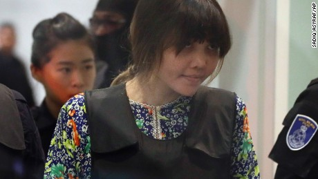 REMOVES REFERENCE TO RE-ENACTMENT - Vietnamese Doan Thi Huong is escorted by police as she arrives at Kuala Lumpur International Airport in Sepang, Malaysia, Tuesday, Oct. 24, 2017.  The two women accused of killing Kim Jong Nam, the North Korean leader's half brother, are touring at the Malaysian airport as participants in the murder trial visit the scene of the attack. (AP Photo/Sadiq Asyraf)