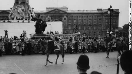 "Queen Elizabeth II rides the horse ""Winston"" past crowds on June 11, 1953."
