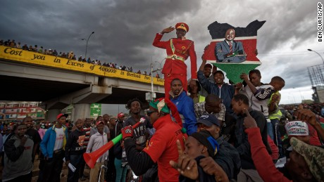 Supporters of Kenya's President Uhuru Kenyatta ride around and cheer, some holding a placard of Kenyatta, as they await his arrival as part of a campaign tour, in Githurai on the outskirts of Nairobi, Kenya Monday, Oct. 23, 2017. Kenyatta said Monday the presidential election must go ahead as planned on Thursday, despite a boycott by the main opposition candidate and the chief electoral officer's recent statement that he cannot guarantee that the polls would be credible.