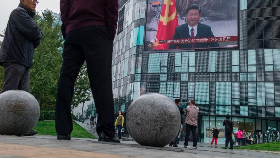 Residents watch a large screen showing Chinese President Xi Jinping revealing the new Politburo Standing Committee, the nation's top decision-making body at the Great Hall of the People in Beijing on October 25, 2017.