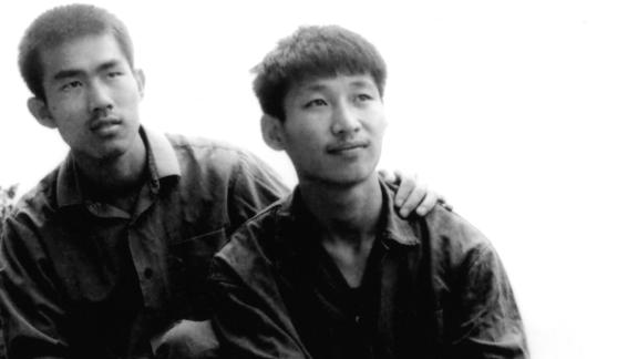 Xi, right, poses for a photo as a college student in 1977.