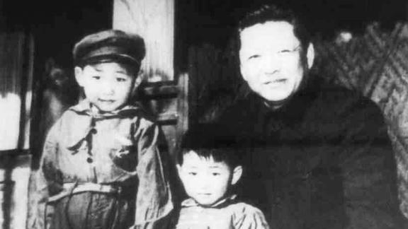 XI, left, stands with his father, Xi Zhongxun, and his younger brother, Xi Yuanping, in 1958. Xi Zhongxun was a communist revolutionary who held several positions in the National People