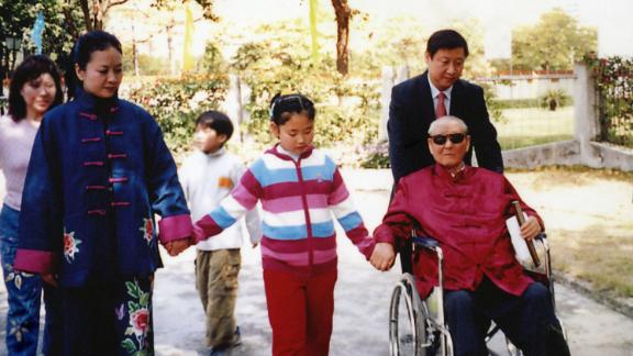 Xi pushes his father as he walks with his wife and his daughter, Xi Mingze, in 2012.