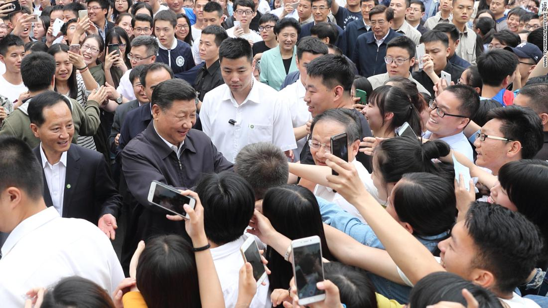 Xi shakes hands with teachers and students while visiting a university in Beijing in May 2017.