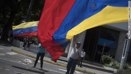 Protester carrying flags on Francisco de Miranda Avenida  during a blockade called by the opposition in Altamira, Caracas on August 8, 2017